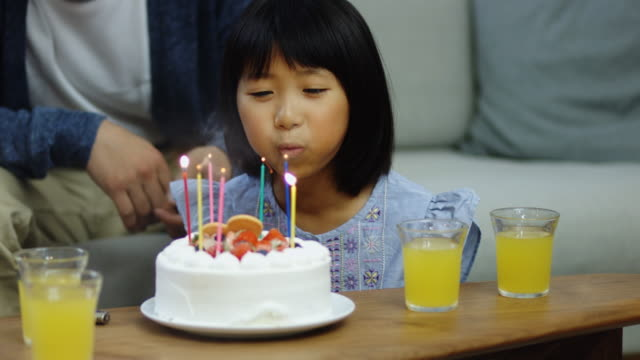 Little Girl Blowing Out Birthday Candles