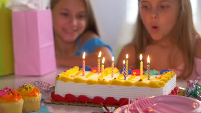vídeos de stock e filmes b-roll de little girl blowing out birthday candles. - soprar