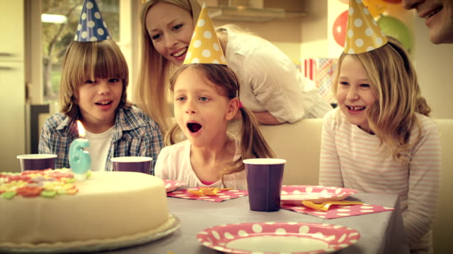 SLO MO little girl blowing out candles on birthday cake