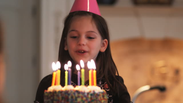 vídeos de stock, filmes e b-roll de little girl blowing out the candles on her birthday cake - aniversário