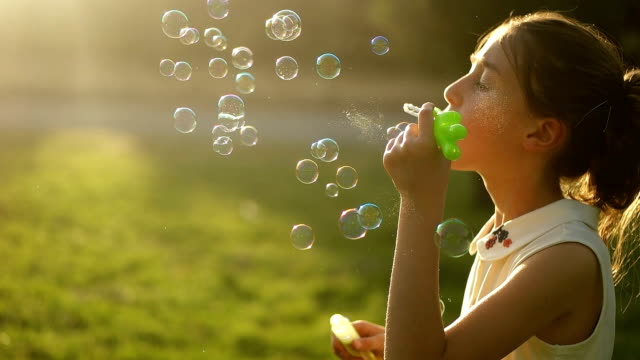 Little girl blowing soap bubbles in park-slowmotion