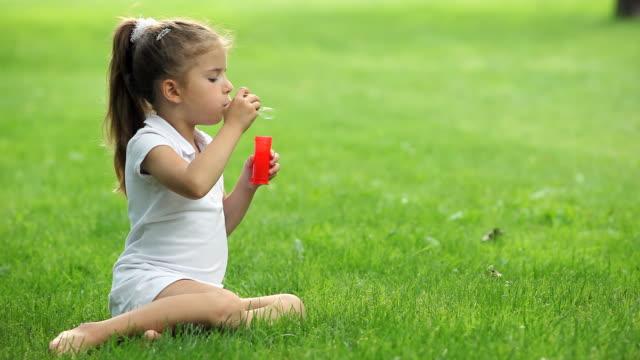 Petite fille souffle des bulles de savon