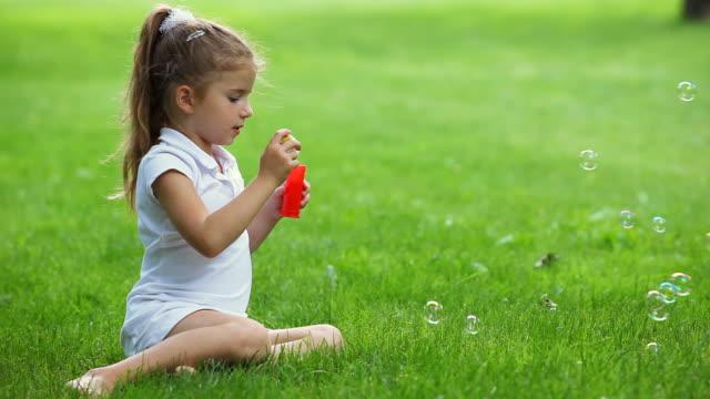 stockvideo's en b-roll-footage met little girl blowing soap bubbles - paardenstaart haar naar achteren
