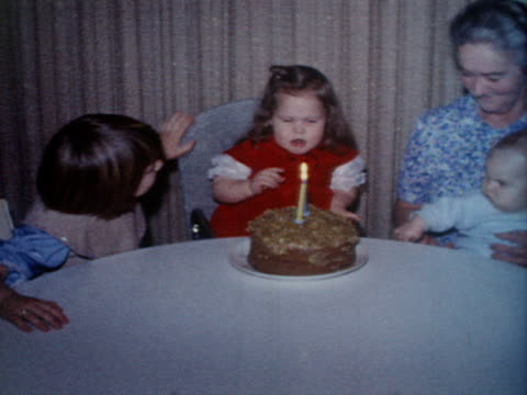 A little girl blows out her sister's birthday candles.