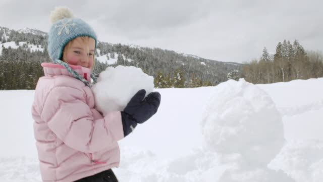 MS PAN Little girl builds up snowman / Sun Valley, Idaho, United States