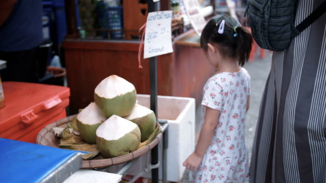 vídeos de stock, filmes e b-roll de menina, compra de coco na comida de rua - vendedor trabalho comercial