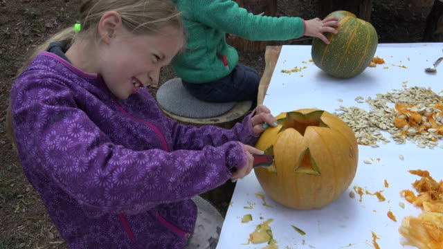 little girl carving a pumpkin by herself outside in the forest playground - carving knife stock videos and b-roll footage