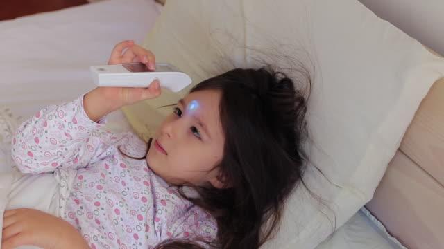 stockvideo's en b-roll-footage met meisje dat haar eigen lichaamstemperatuur met infrarode thermometer controleert - dubbel bed