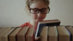 Little Girl Child Choose Books on Shelf. Young Schoolgirl in Glasses Taking Books From Shelf and Flipping Through Pages in Library.  Book Reading Hobby.