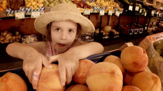 little girl choosing fruit at farmers market. summer resort - greengrocer's shop stock videos & royalty-free footage