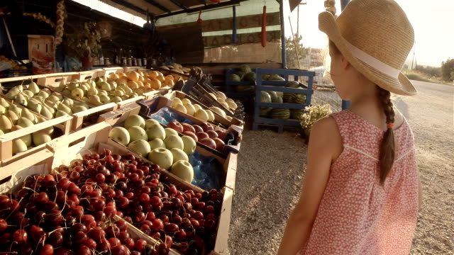 Little Girl Choosing Fruit At Farmers Market