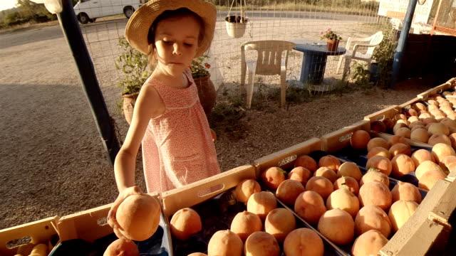 ファーマーズ ・ マーケットで果物を選択する少女