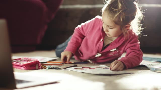 vídeos de stock, filmes e b-roll de uma garotinha escolhendo lápis e fazendo lição de casa no chão na sala de estar - vídeo de estoque de estoque de estoque - bebês meninas