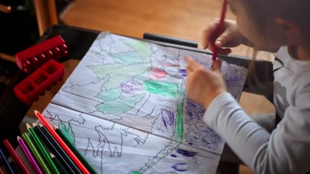 vidéos et rushes de une petite fille choisissant le crayon et faisant des devoirs sur la table dans le salon-vidéo de stock - illustration