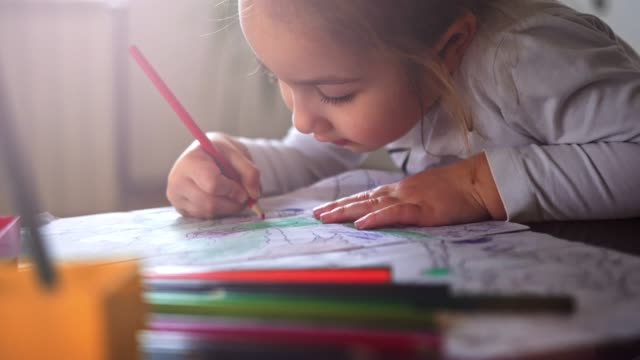 a little girl choosing pencil and doing homework on table in living room - stock video - drawing activity stock videos & royalty-free footage