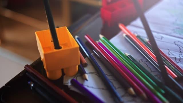 vídeos de stock, filmes e b-roll de uma menina que escolhe o lápis e que faz trabalhos de casa na tabela na sala de visitas-vídeo stock - cômodo de casa
