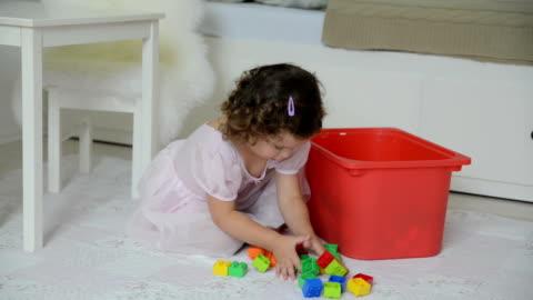 vídeos y material grabado en eventos de stock de little girl limpieza coloridos los juguetes para niños - habitación
