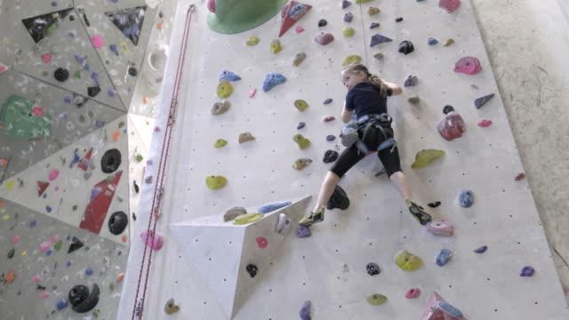 little girl climbing on indoor climbing wall - climbing equipment stock videos & royalty-free footage