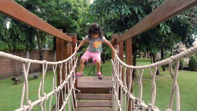 a little girl climbing on ropes at playground - playground stock videos & royalty-free footage