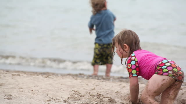 ms ts little girl climbing out of hole in sand at beach and going wash her hands in water / toronto, ontario, canada - kelly mason videos stock videos & royalty-free footage
