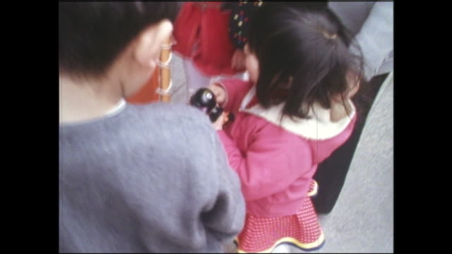 A little girl clutches a miniature Dakko-Chan doll as a larger Dakko-Chan appears to climb a clock pillar on the Ginza.