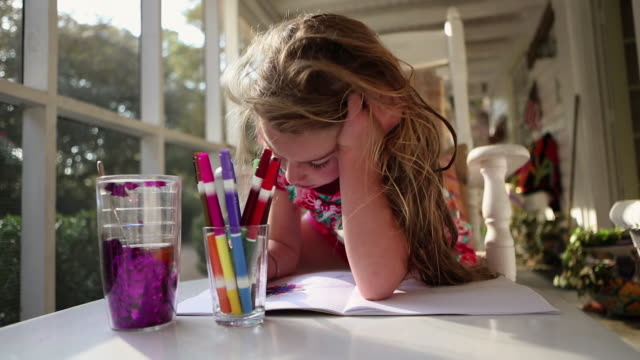 MS Little girl coloring on screened porch / St. Simon's Island, Georgia, United States