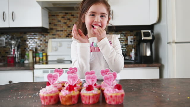 little girl cooking valentine muffins with grandmother - valentine's day stock videos & royalty-free footage