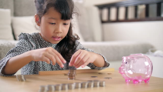 little girl counting a coin for saving money for the future - organisation stock videos & royalty-free footage