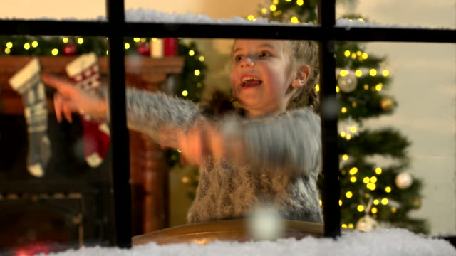 Little Girl counting Snow falling through window at Christmas