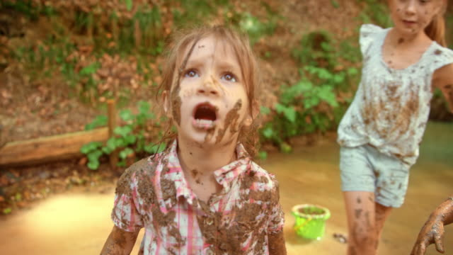 slo mo little girl covered in mud all over her hair and shirt - fango video stock e b–roll