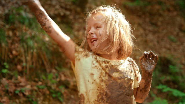 slo mo little girl covered in mud from head to toe throwing mud from a green bucket and laughing - mud stock videos & royalty-free footage