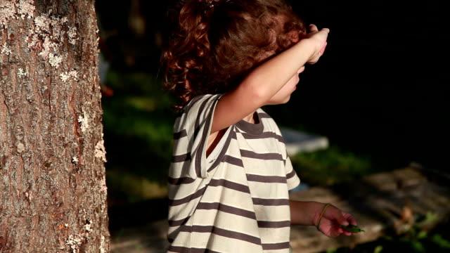 vídeos de stock, filmes e b-roll de menina que cobre olhos do sol brilhante - mãos cobrindo olhos