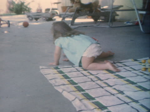 a little girl crawls around a patio with her baby sister. - krabbeln stock-videos und b-roll-filmmaterial