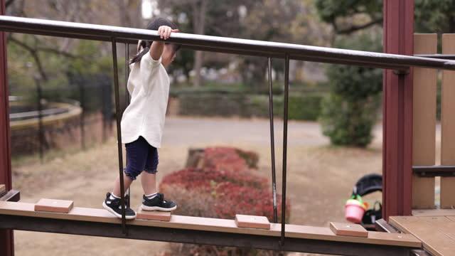 vidéos et rushes de petite fille traversant le pont dans le terrain de jeu par elle-même - partie 1 de 2 - son