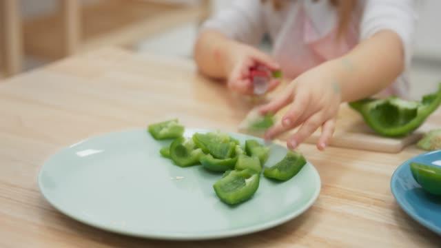 little girl cutting a green pepper - green bell pepper stock videos & royalty-free footage