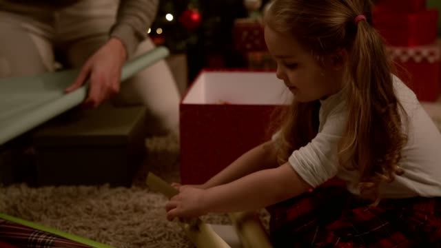little girl cutting wrapping paper with scissors - christmas wrapping paper stock videos & royalty-free footage