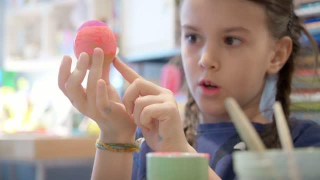 vídeos de stock e filmes b-roll de little girl decorating easter egg in children's room - desenhar