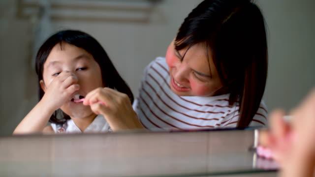 vidéos et rushes de petite fille avec diligence se brosser les dents dans la salle de bain - dents