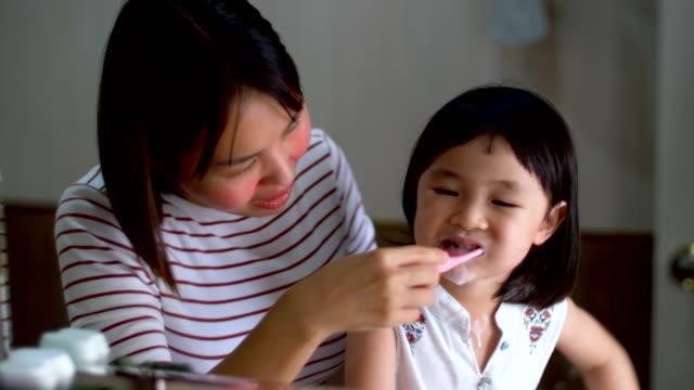 小さな女の子が熱心にバスルームで歯を磨く - 洗う点の映像素材/bロール