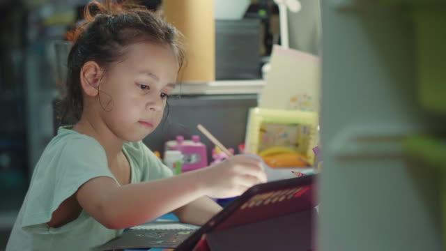 vídeos de stock e filmes b-roll de a little girl do homework with digital tablet. - bebés meninas