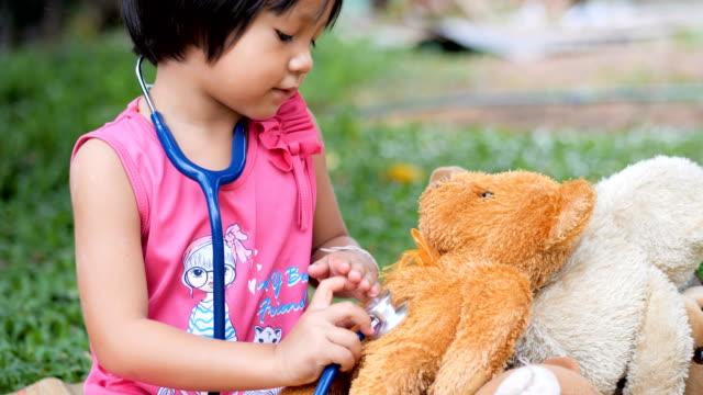 little girl doctor saving her teddy bear friend - stethoscope stock videos & royalty-free footage