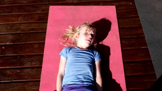 little girl does some sit-ups on an exercise mat - sit ups stock videos & royalty-free footage