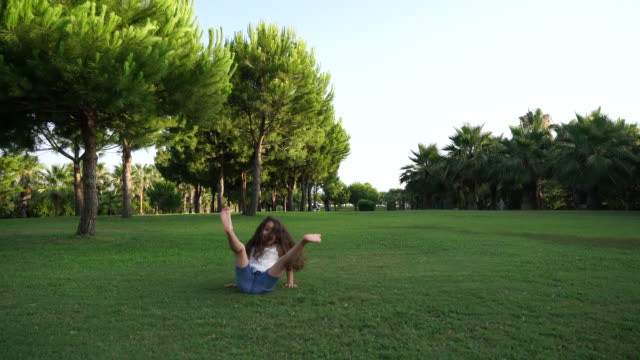 little girl doing cartwheel on meadow - cartwheel stock videos & royalty-free footage