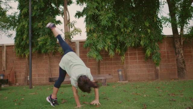 little girl doing cartwheels in garden. - cartwheel stock videos & royalty-free footage
