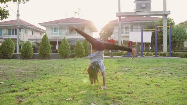 little girl doing cartwheels in park. - cartwheel stock videos & royalty-free footage
