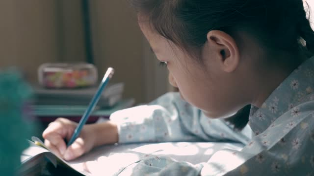 little girl doing her homework - note pad stock videos & royalty-free footage