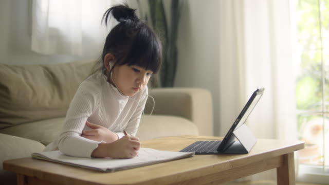 little girl doing her homework with digital tablet. - elementary student stock videos & royalty-free footage