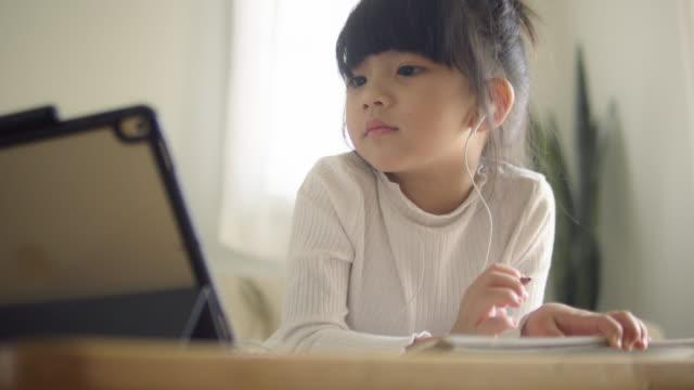kleines mädchen macht ihre hausaufgaben mit digitalen tablet. - tablet benutzen stock-videos und b-roll-filmmaterial