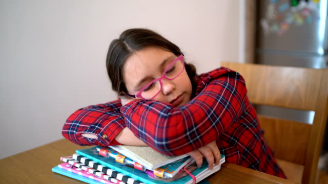 机の上の学校のために家庭の仕事をしている少女 - 学校備品点の映像素材/bロール