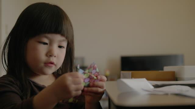 vidéos et rushes de petite fille faisant l'origami à la maison. - origami